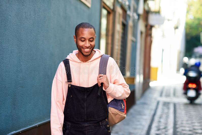 Junges gehendes Lächeln des schwarzen Mannes hinunter die Straße stockfotos