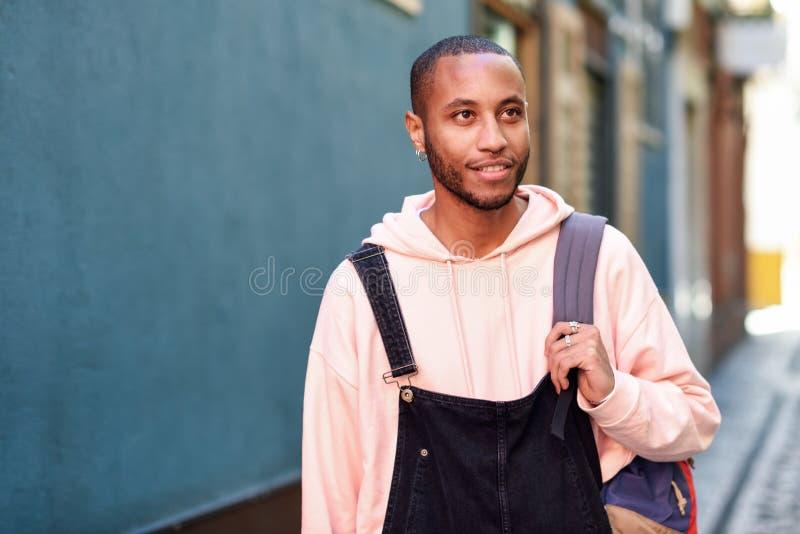 Junges gehendes Lächeln des schwarzen Mannes hinunter die Straße lizenzfreie stockfotos