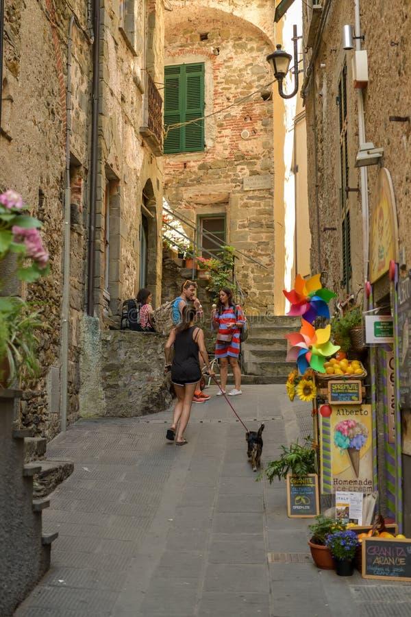 Junges gehendes Mädchen ihr Hund durch schmale Straßen in Corniglia lizenzfreie stockfotografie