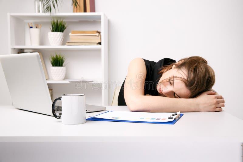 Junges Geschäftsfraugefühl schläfrig an ihrem Arbeitsplatz im Büro stockfotos