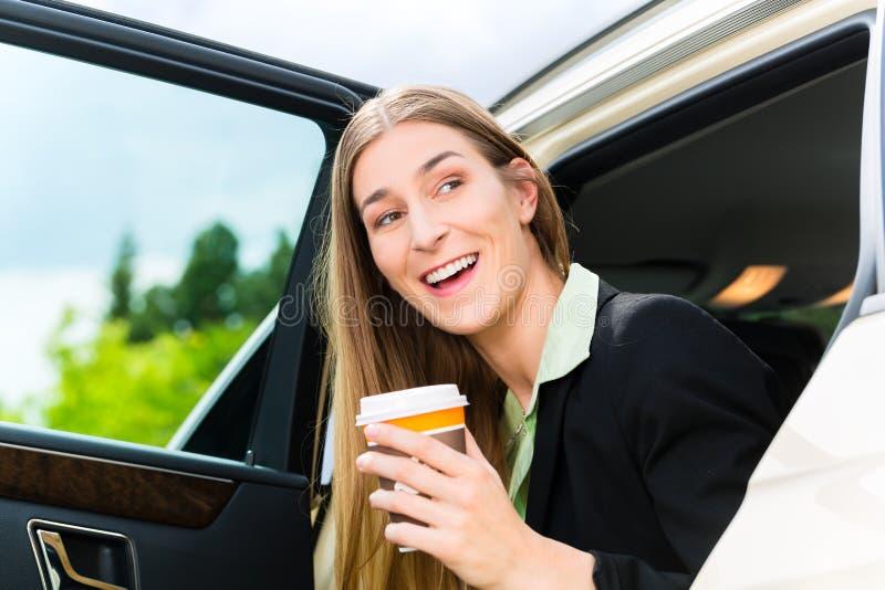 Junges Geschäftsfrauverlassen ein Taxi lizenzfreie stockfotografie