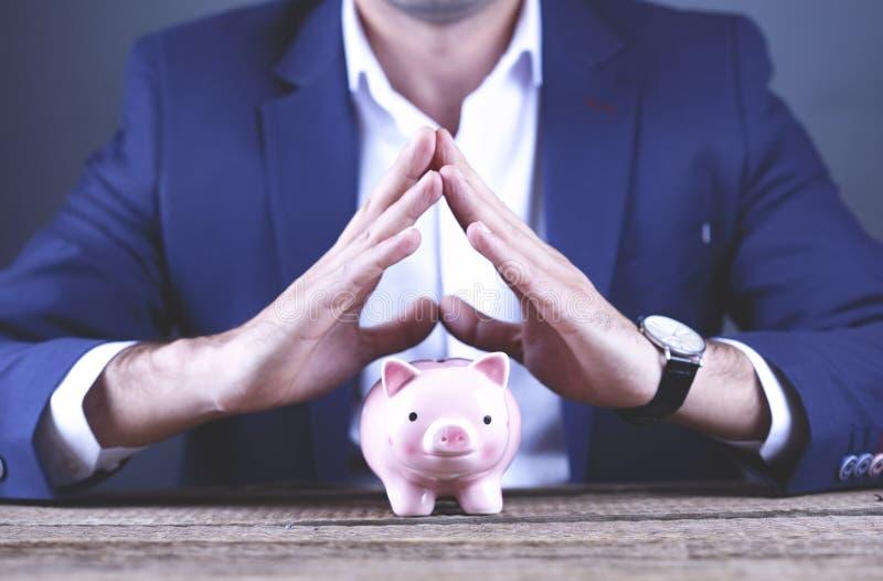 Junges Geschäftsmann-Handholdingsparschwein stockfotografie