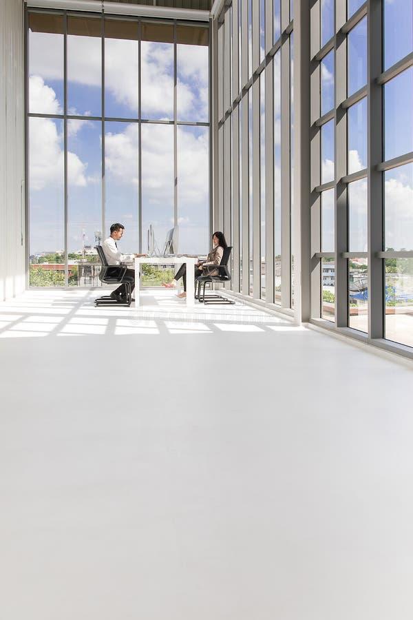 Junges Geschäftsmann- und Frauensitzen, Unterhaltung und Arbeits-togeth lizenzfreies stockfoto