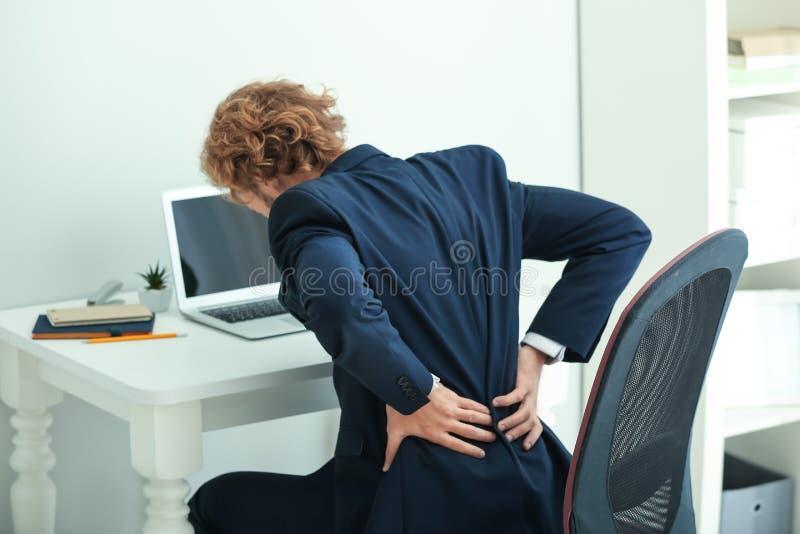 Junges Geschäftsmannleiden von den Rückenschmerzen im Büro lizenzfreie stockbilder