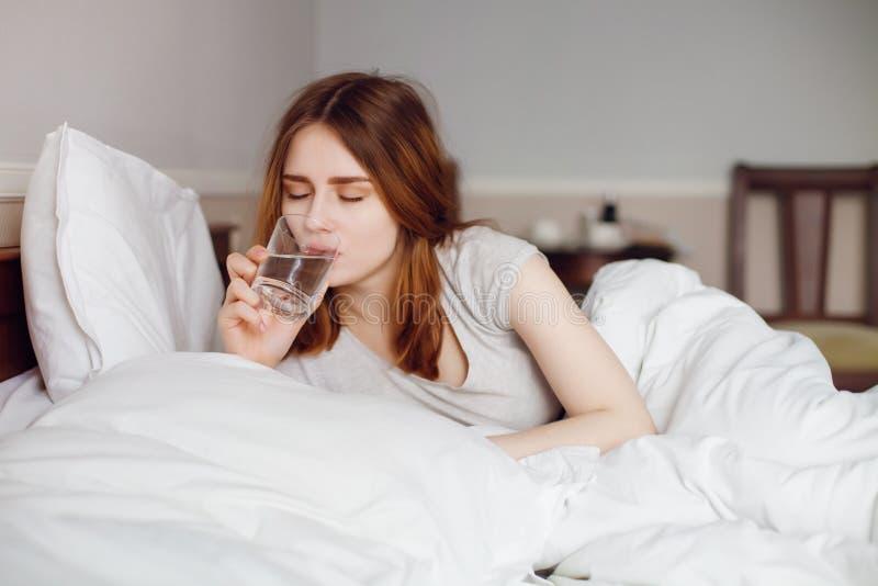 Junges gesundes Mädchengetränkwasser in ihrem Bett auf Morgen lizenzfreies stockfoto