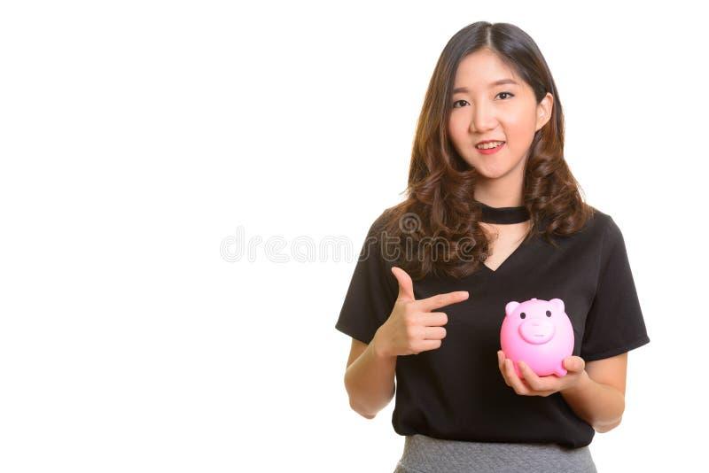 Junges glückliches asiatisches Geschäftsfrauholdingsparschwein und -c$zeigen lizenzfreies stockfoto