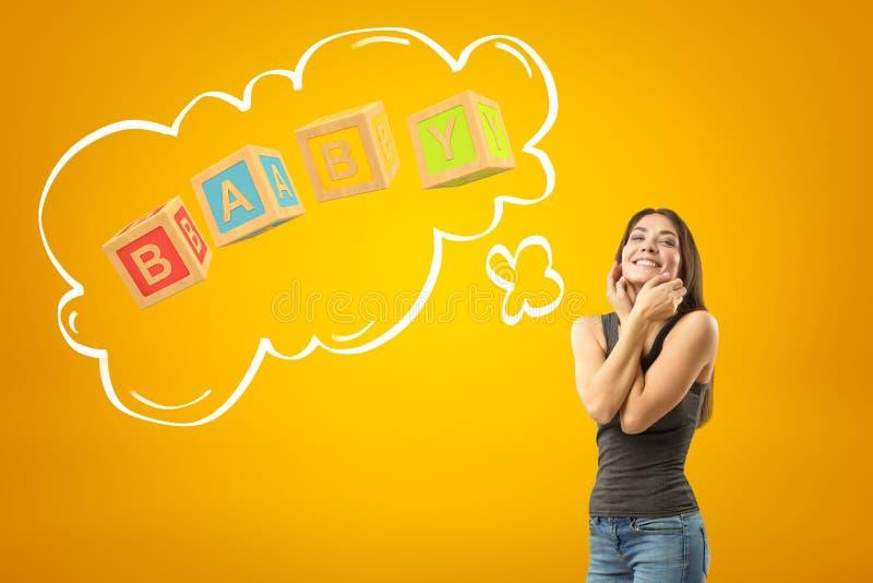 Junges glückliches brunette Mädchen in der zufälligen Kleidung mit BABYbauklötzen unterzeichnen auf gelbem Hintergrund stockfotografie
