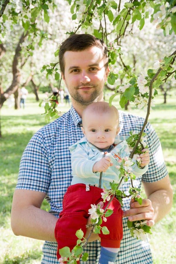 Junges glückliches Familiengehen im Freien Bringen Sie Griffkind auf Händen hervor und freuen Sie sich Sie sind zusammen glücklic stockfotografie