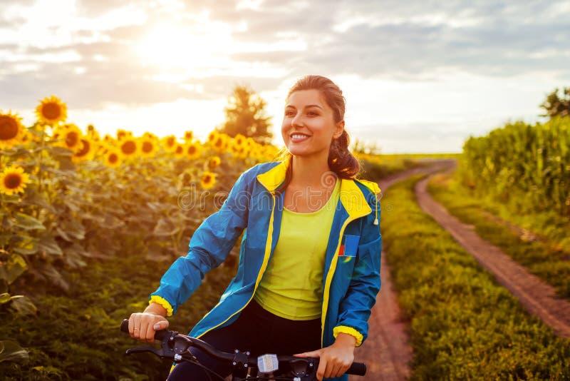 Junges glückliches Frauenradfahrer-Reitfahrrad im Sonnenblumenfeld Sommer-Sport-T?tigkeit Gesunder Lebensstil lizenzfreie stockfotos
