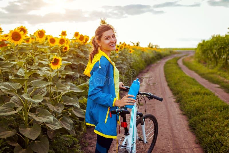 Junges glückliches Frauenradfahrer-Reitfahrrad im Sonnenblumenfeld Sommer-Sport-T?tigkeit Gesunder Lebensstil stockbild