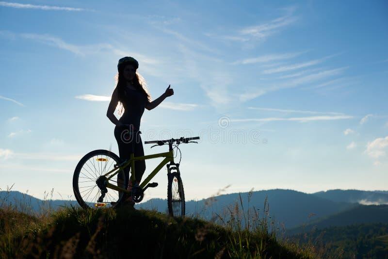 Junges glückliches Frauenreitfahrrad in den Bergen am Sommertag lizenzfreie stockfotografie