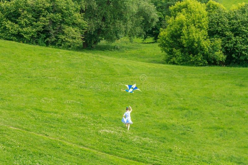 Junges glückliches Kindermädchen, das mit hellem Drachen im Park spielt stockfoto