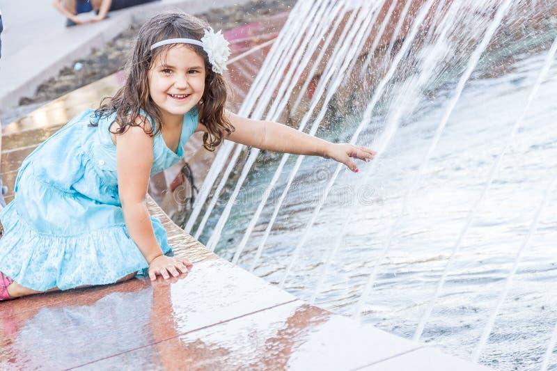 Junges glückliches Kindermädchen, das mit Wasserbrunnen, Hafen im Freien spielt lizenzfreie stockbilder