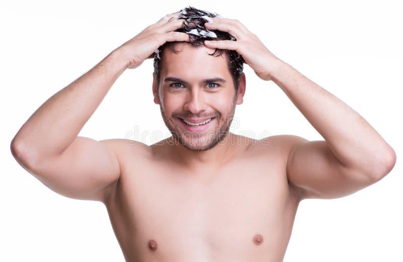 Junges glückliches lächelndes waschendes Haar des Mannes. lizenzfreie stockbilder