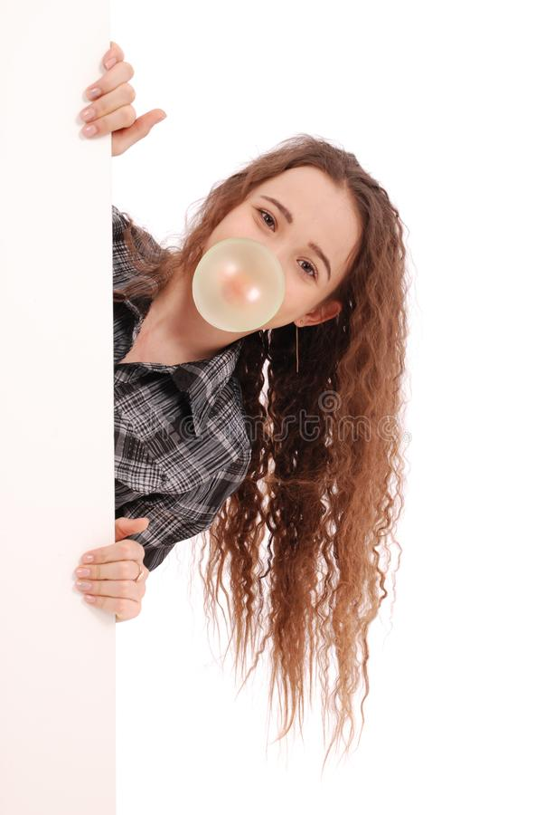 Junges glückliches Mädchen, das einen Kaugummi durchbrennt stockfoto