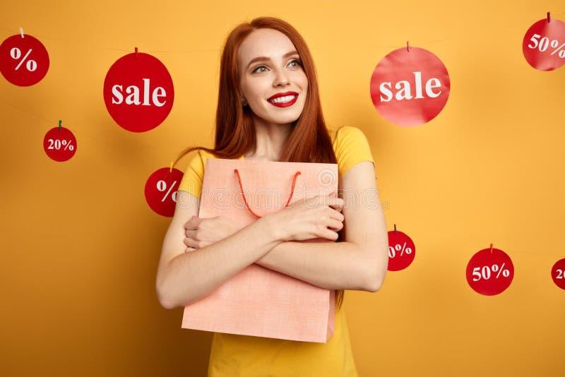 Junges glückliches Mädchen, das ihre Einkaufstasche auf gelbem Hintergrund umarmt lizenzfreie stockfotografie