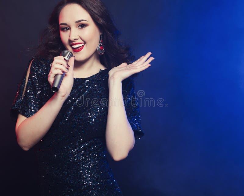 Junges glückliches Mädchen, das in Mikrofon an der Partei singt stockfoto