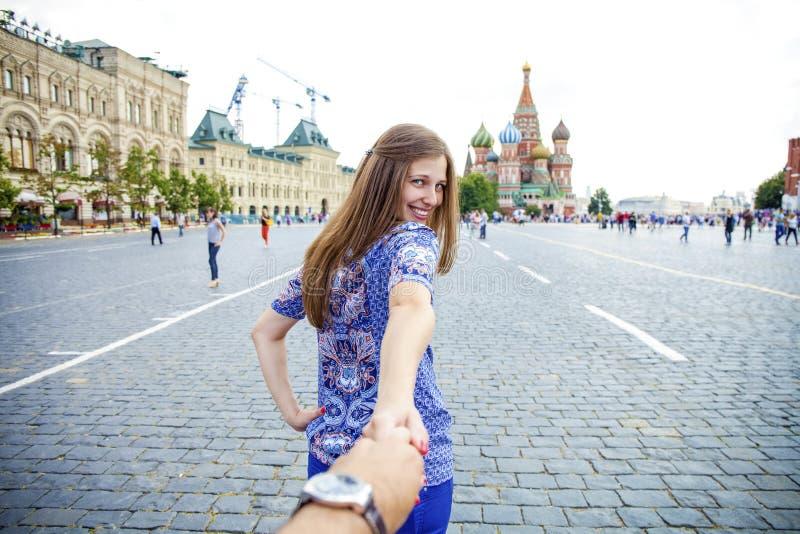Junges glückliches Mädchen zieht die Kerlhand auf dem Roten Platz in Moskau lizenzfreie stockfotografie