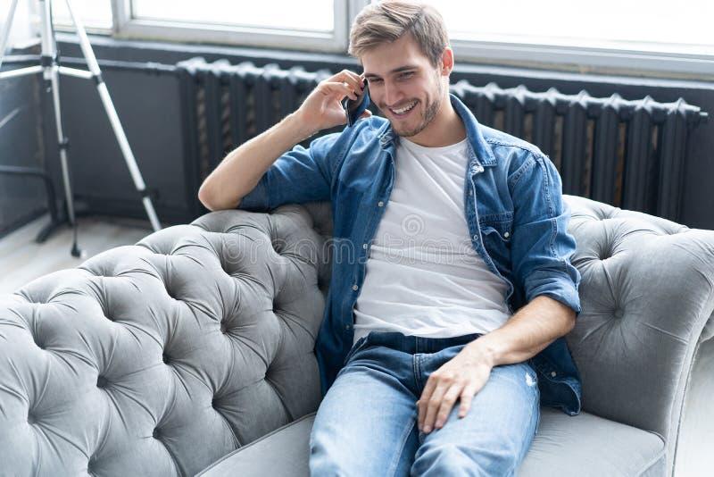 Junges glückliches Mann-Sitzen entspannt auf Sofa und Unterhaltung am Telefon lizenzfreie stockfotografie