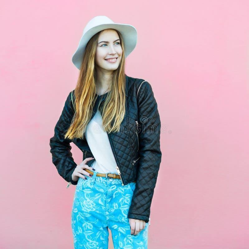 Junges glückliches Mode Bloggermädchen, das nahe der Wand trägt zufällige Straßenartausstattung aufwirft stockbilder