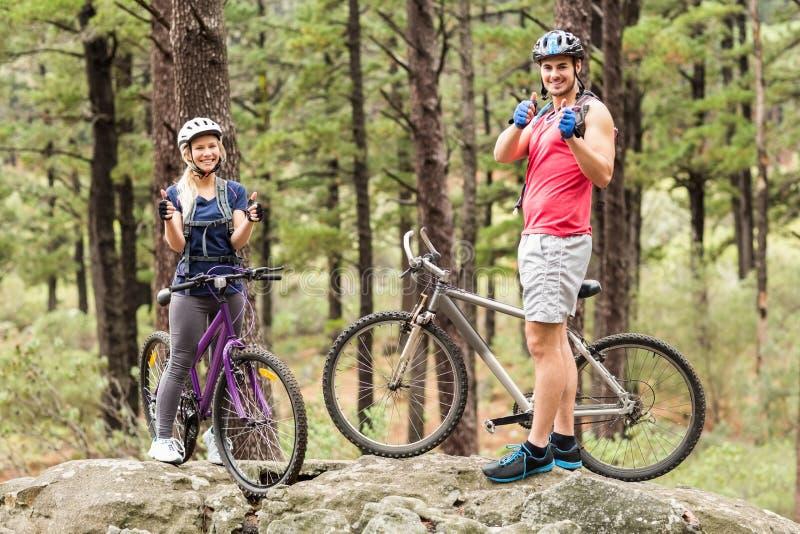 Junges glückliches Paar auf den Fahrrädern, die Kamera mit den Daumen oben betrachten stockbild