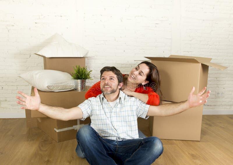 Junges glückliches Paar, das auf dem Boden zusammen feiert das Bewegen in neues flaches Haus oder in Wohnung sitzt stockbild