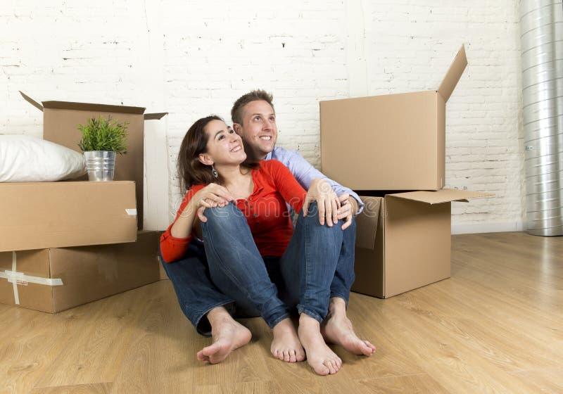 Junges glückliches Paar, das auf dem Boden zusammen feiert das Bewegen in neues flaches Haus oder in Wohnung sitzt lizenzfreies stockbild