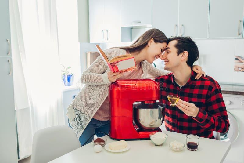 Junges glückliches Paar, das auf Küche mit Küchenmaschine kocht Frauen- und Mannleserezept und -c$umarmen stockfotos