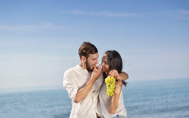 Junges glückliches Paar, das Datum an der Küste hat lizenzfreie stockbilder