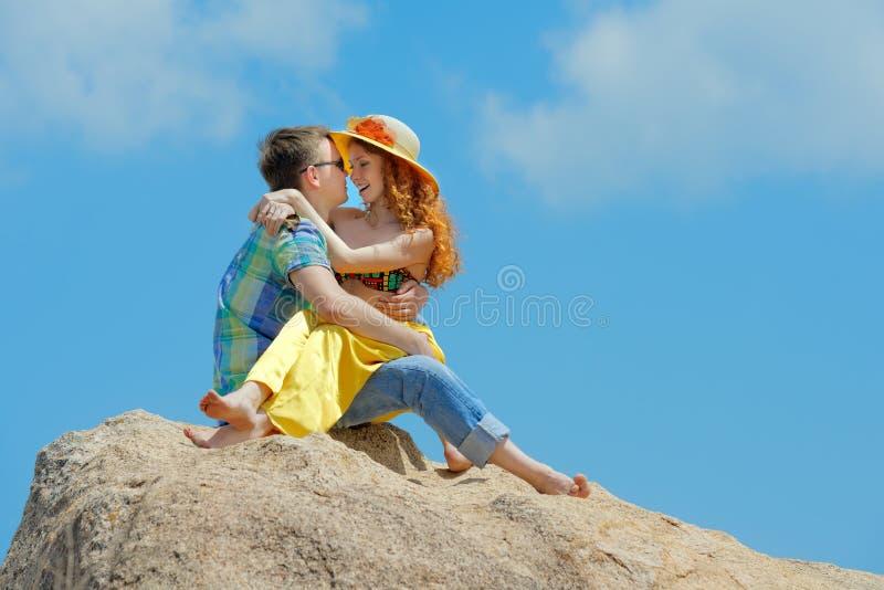 Junges glückliches Paar, das in den Bergen sitzt stockbild