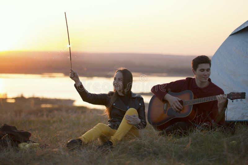 Junges glückliches Paar, das den Spaß zusammen spielt Gitarre auf dem hil hat stockfotos