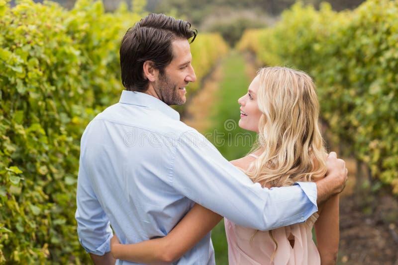 Junges glückliches Paar, das einen Arm um einander und das Lächeln hat stockfotos