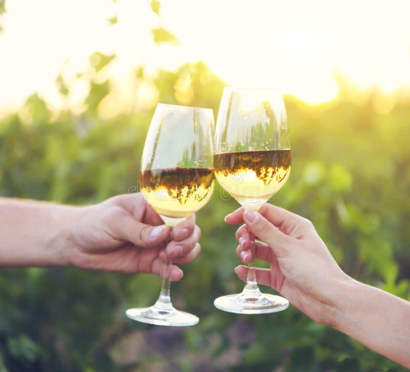 Junges glückliches Paar, das Gläser weißen Wein genießt lizenzfreie stockfotos