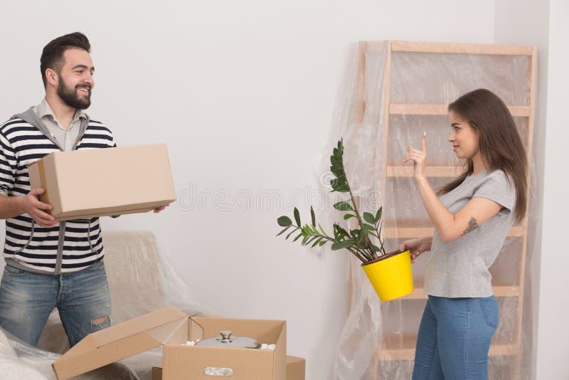 Junges glückliches Paar, das Kästen nachdem dem Bewegen in neues Haus auspackt stockfotos