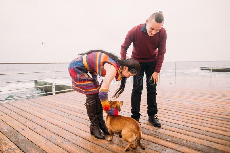 Junges glückliches Paar, das mit Hund auf dem regnerischen Liegeplatz im Herbst geht Sun-Strahl in den Fjorden stockbilder