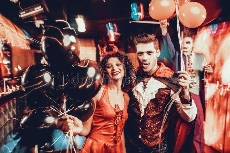 Junges glückliches Paar in den Kostümen an Halloween-Partei lizenzfreies stockfoto