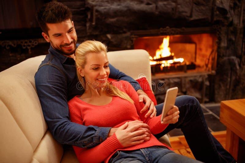 Junges glückliches Paar in der Liebe unter Verwendung des Handys zusammen lizenzfreie stockfotos