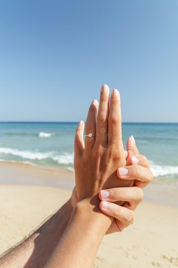 Junges glückliches Paar erhält sich engagierte im Heiratsantrag auf Strand lizenzfreie stockfotografie