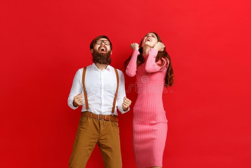 Junges glückliches Paar gewann Gewinn auf farbigem rotem Hintergrund emotional feiern stockbild