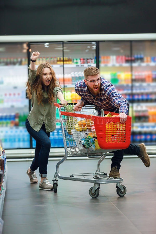 Junges glückliches Paar mit dem Lebensmittelwarenkorb, der das Lebensmittelgeschäfteinkaufen tut lizenzfreie stockbilder