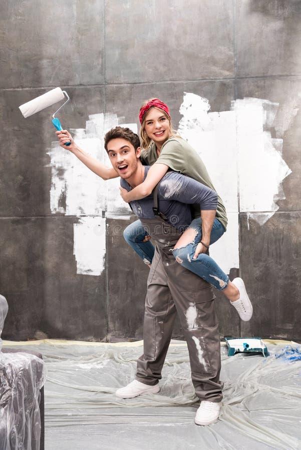Junges glückliches Paar mit der Farbenrolle, die Spaß hat stockfotos