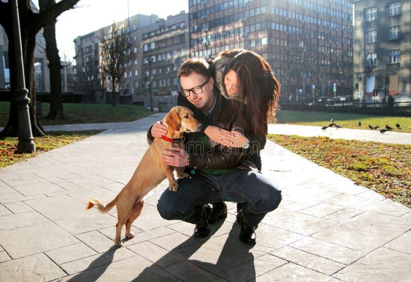 Junges glückliches Paar mit Hund genießen an einem schönen Tag lizenzfreies stockbild