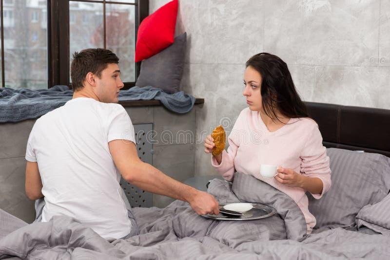 Junges glückliches Paar wachte gerade auf und im Bett frühstückend lizenzfreie stockfotografie