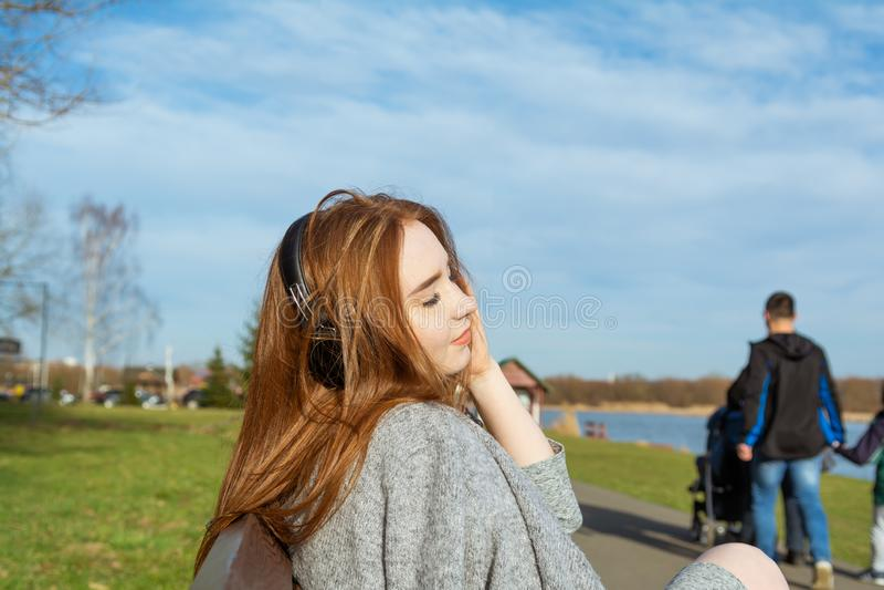 Junges, glückliches Rothaarigemädchen im Frühjahr im Park nahe dem Fluss hört Musik durch drahtlose bluetooth Kopfhörer lizenzfreies stockfoto