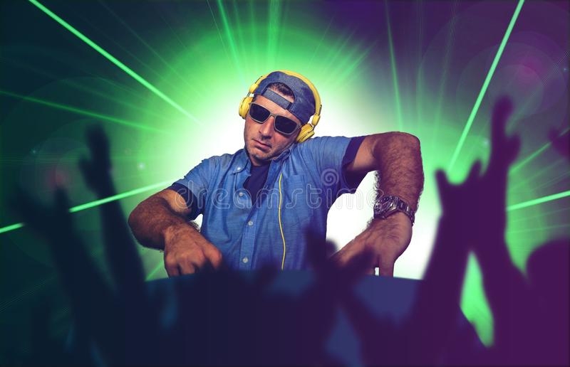 Junges glückliches und kühles DJ, das Musik am Parteiereignis in Nachtklub mischenden techno Liedern auf Laser und Blitzlichthi stockfotografie