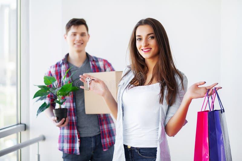 Junges gl?ckliches Paar, das in ihr neues Haus umzieht Sie auspackend und neues Reinigungshaus lizenzfreie stockfotografie