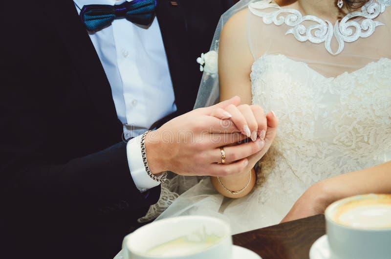Junges Händchenhalten des verheirateten Paars, Zeremoniehochzeitstag lizenzfreie stockfotos
