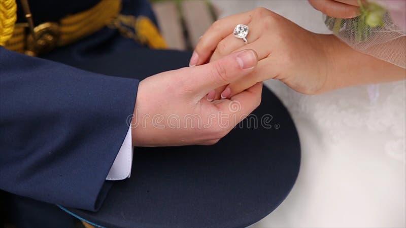 Junges Händchenhalten des verheirateten Paars, Zeremoniehochzeitstag Schließen Sie herauf Bräutigam Put den Ehering auf Braut lizenzfreie stockbilder