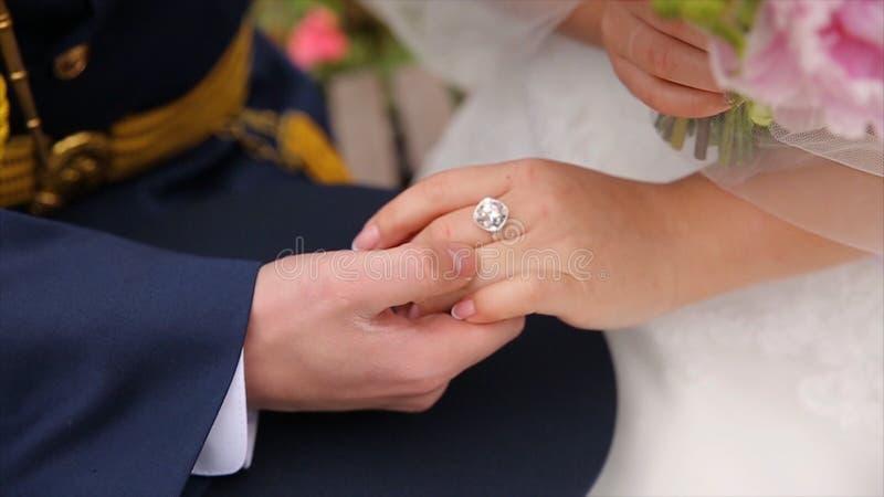 Junges Händchenhalten des verheirateten Paars, Zeremoniehochzeitstag Schließen Sie herauf Bräutigam Put den Ehering auf Braut stockfotos