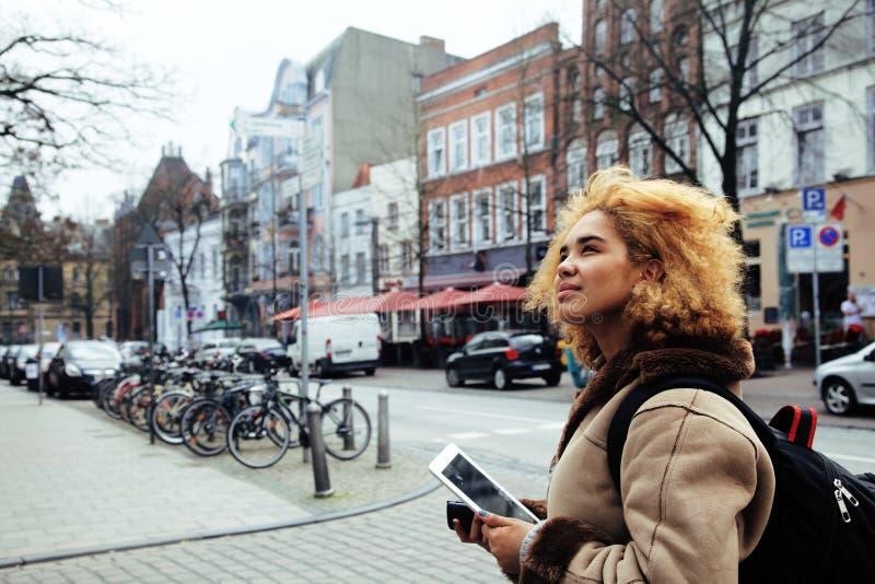 Junges hübsches Afroamerikanermädchen mit dem gelockten Haar, das herein Foto auf einer Tablette, Lebensstilleutekonzept, Tourist stockfoto